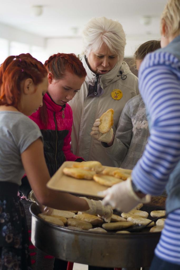 Päikeselaagri patroon Marina Kaljurand ühes laagrilistega valmistamas räimeburgerit